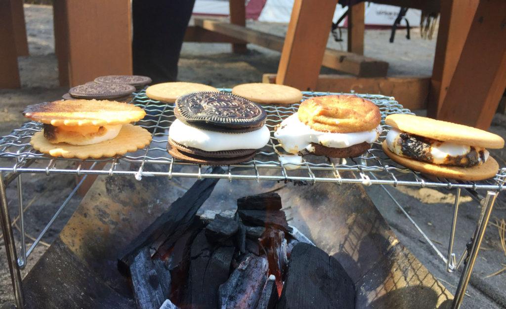 炭火の上で焼かれるビスケットとマシュマロ。