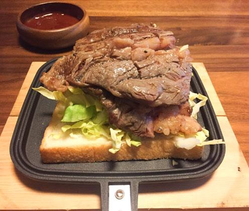 ホットサンドメーカーにはさんだ2枚重ねのステーキ。