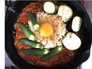 カレーにお冷ご飯をのせ、夏野菜と卵ものせ、一緒に蒸す。