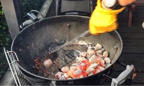 バーベキューコンロの半分に炭を寄せる